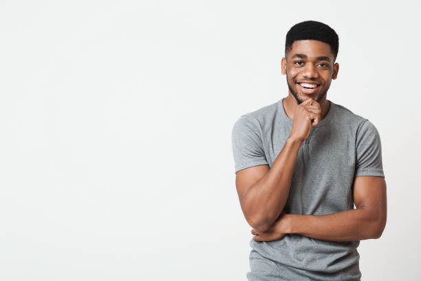 Interested smiling african-american man touching chin, copy space stock photo