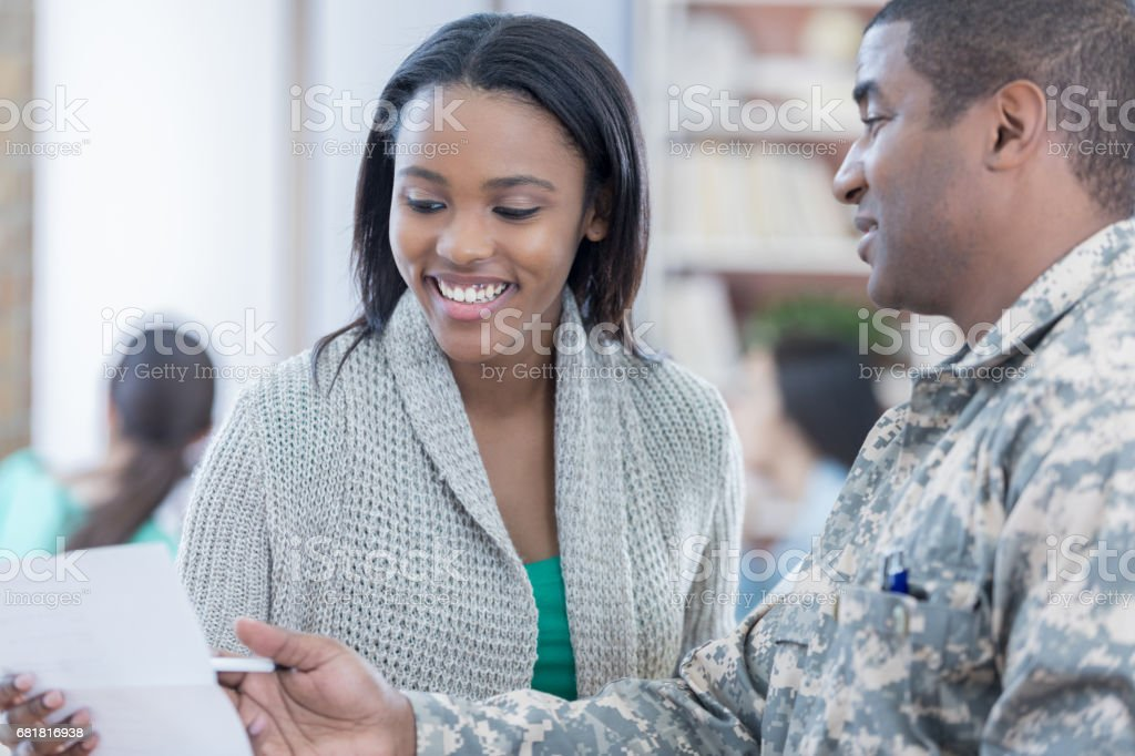 Interested young woman listens to military recruiter stock photo