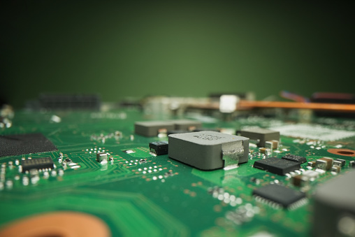 Macrophotography of an electronic circuit board in green-aquamarine tones, with golden wires and electrical components