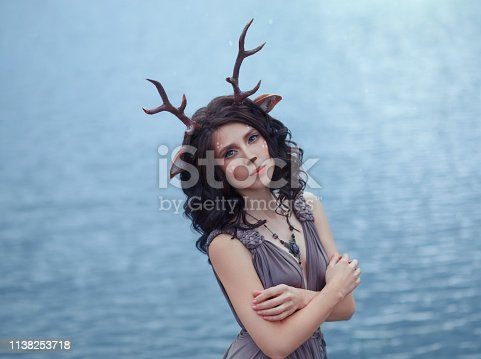 interesting photo of mother deer in front of lagle lake, characters of the fairy forest, image of a sad woman-faun near a large lake, unusual makeup, with homemade horns and ears on dark curly hair.