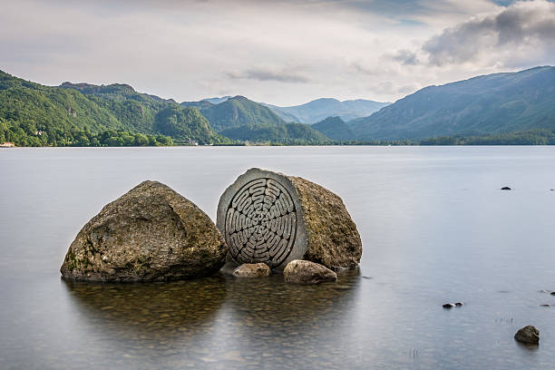 Interesting Rocks With Beautiful Cloudy Sky At Derwentwater In Keswick. stock photo