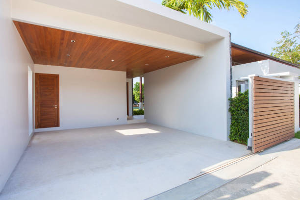 Interior and exterior design of white carport with wooden ceiling and wooden gated area stock photo