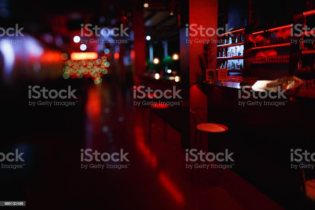 Interior and furniture of the night bar with red lighting. Bar stools are at the bar, photographed on the lens tilt-shift zbiór zdjęć royalty-free
