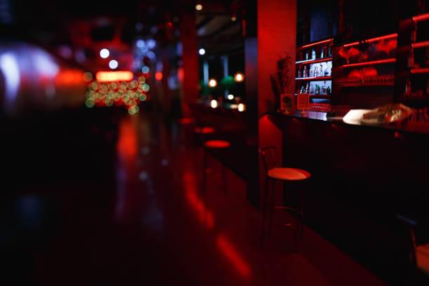 interieur und möbel von der nachtbar mit roter beleuchtung. barhocker sind an der bar, auf das tilt-shift-objektiv fotografiert - neon partylebensmittel stock-fotos und bilder