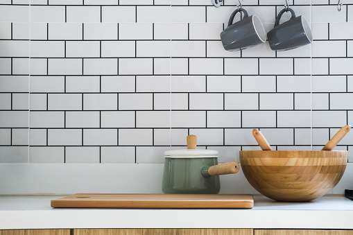 Close-up kitchen room with pot, chopping wood, wooden tub and two ceramic coffee cup put on modern counter, interior and home decor on modern style