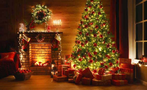 インテリアクリスマス。魔法の輝く木、暖炉、暗闇の中の贈り物 - クリスマス ストックフォトと画像