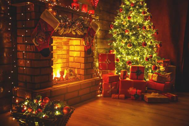 interior christmas. magic glowing tree, fireplace gifts in  dark - christmas background стоковые фото и изображения