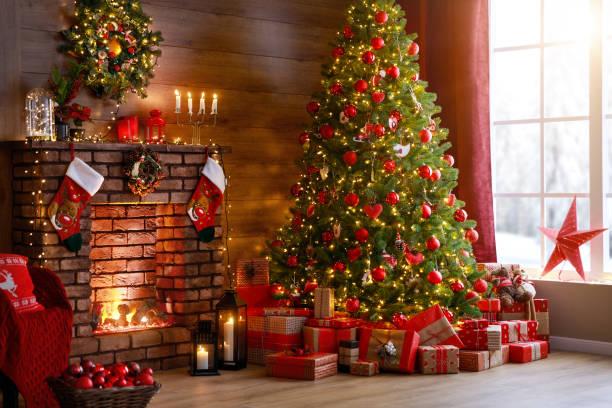 интерьер рождество. волшебное светящееся дерево, камин, подарки - christmas background стоковые фото и изображения