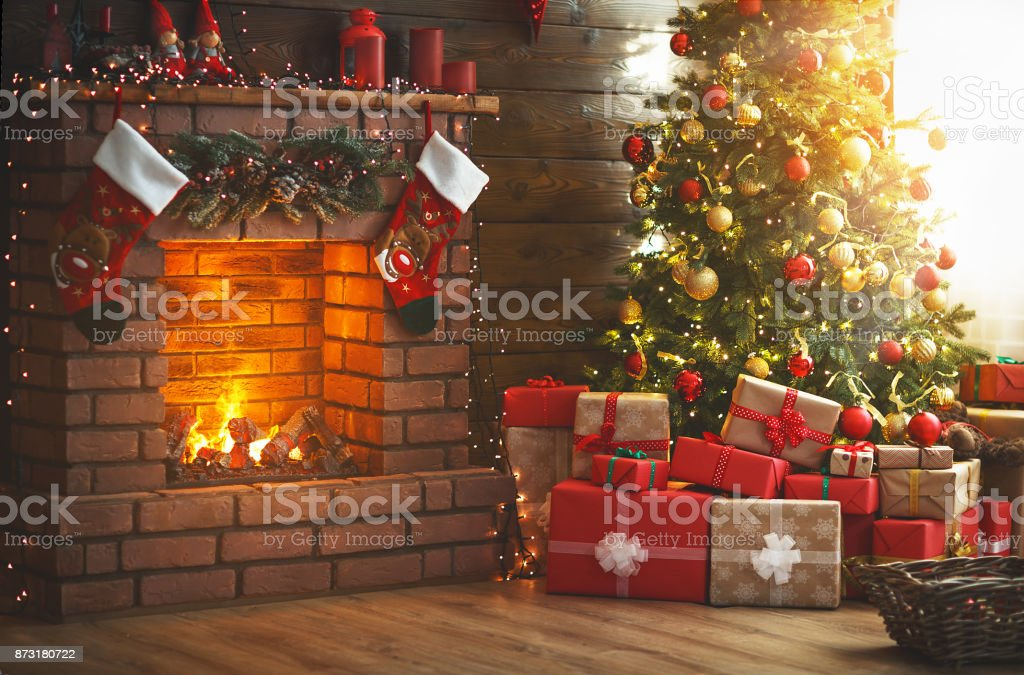 interior christmas. magic glowing tree, fireplace, gifts stock photo