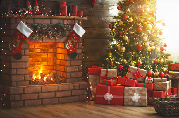 interior christmas. magic glowing tree, fireplace, gifts - christmas stock photos and pictures
