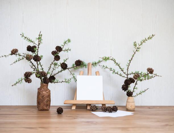 Interior Design Desktop mit Mock-up Poster Frame. Leere Papierkarte Mockup auf einer kleinen Staffelei und Lärchen zweizweigigen mit Kegeln. Stilvolle minimale Home Decor – Foto