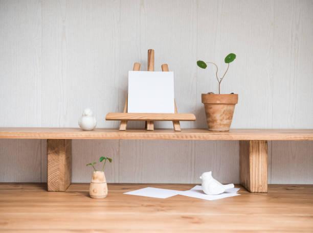 Interior Design Desktop mit Mock-up Poster Frame. Leere Papierkarte Mockup auf einer kleinen Staffel eidesziehend mit Hauspflanzen. Stilvolle minimale Home Decor – Foto