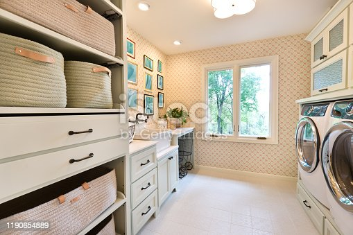 +++NOTE TO INSPECTOR+++ Framed photo on the wall are taken by me, and it is currently in iStock collection +++  Showcase interior design of a utility laundry room in a residential home in United States. with utility sink and fixture, washer and dryer, storage area.