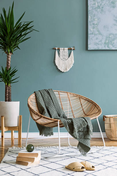 Interior design of living room at modern home with stylish rattan armchair, plaid, macrame, basket, books, tropical plants and elegant accessories. Design home decor. Template. Abstract paintings stock photo
