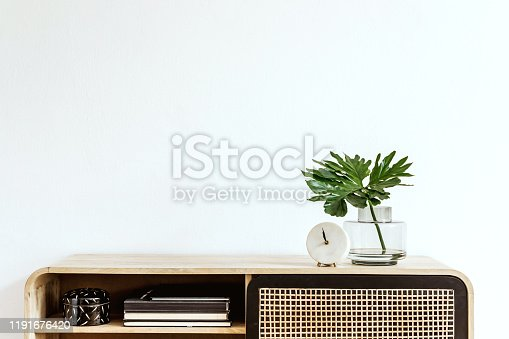 istock Interior design of living room at scandinavian apartment with stylish commode, tropical leaf in vase, books, white clock and elegant accessories. Modern home decor. Template. Copy space. White walls. 1191676420