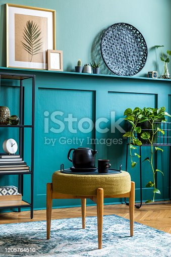 Stylish interior of living room with design furniture and elegant personal accessories. Wood panelling with shelf. Modern home decor. Mock up poster frames. Template