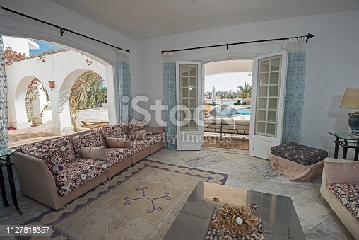 Living room lounge area in luxury holiday villa show home showing interior design decor furnishing and view to swimming pool