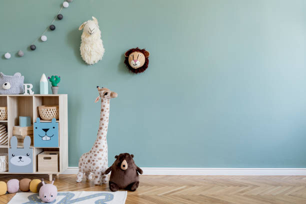 Interior design of scandinavian childroom with wooden cabinet, a lot of plush and wooden toys and accessories. Eucalyptus color of background walls. Plush animal head on the wall. Template Copy space stock photo