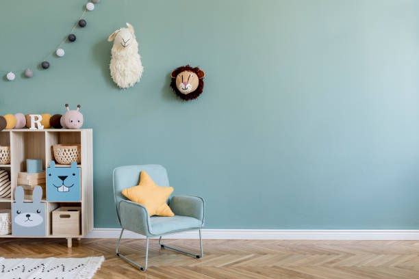 Interior design of scandinavian childroom with wooden cabinet, mint armchair, a lot of plush and wooden toys. Eucalyptus color of background walls. Plush animal head on the wall. Template Copy space stock photo