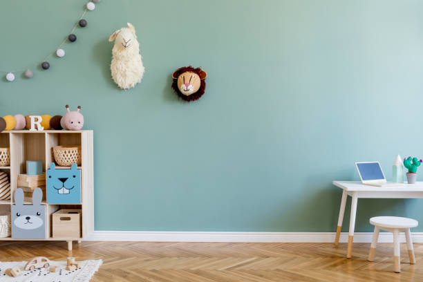 Interior design of scandinavian childroom with wooden cabinet, mint armchair, white desk, a lot of plush and wooden toys. Eucalyptus color of background walls. Plush animal head on the wall. Template stock photo
