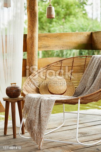 istock Interior design of summer gazebo by the lake with stylish rattan armchair, coffee table, sofa, pillows, plaid and elegant accessories in modern decor. Summer vibes. Chillout. Template. 1271691410
