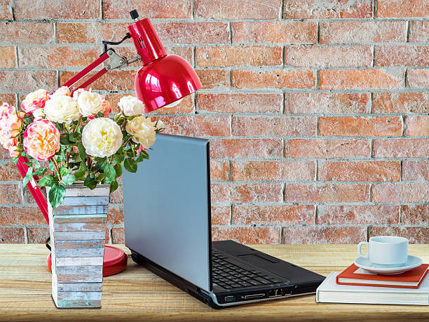 Royalty Free Modern Office Desk With Laptop Lamp And Vase Of Flowers