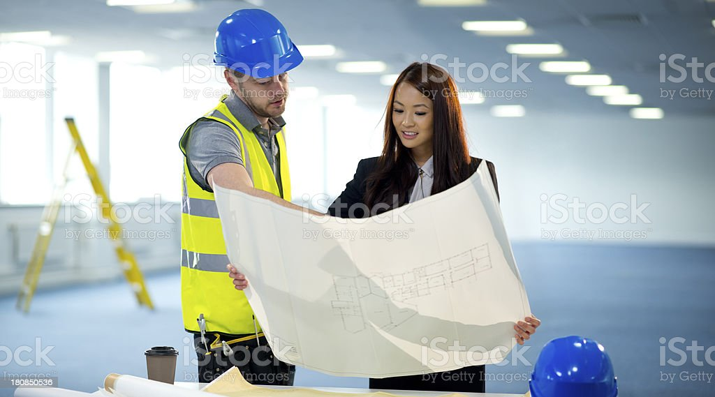 interior designer chats to office contractor royalty-free stock photo