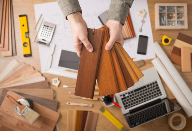 Interior designer choosing a baseboard Professional interior designer holding wood swatches for baseboard and skirting, hands close up with desktop on background interior designer stock pictures, royalty-free photos & images