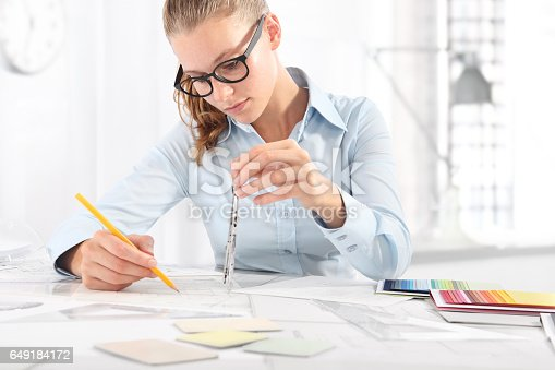 istock interior designer draws at desk in office, with pencil and compass 649184172