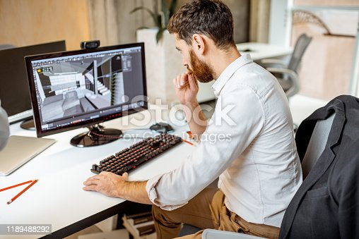 Thoughtful office employee working as an interior designer, 3d modeling on the computer in the office