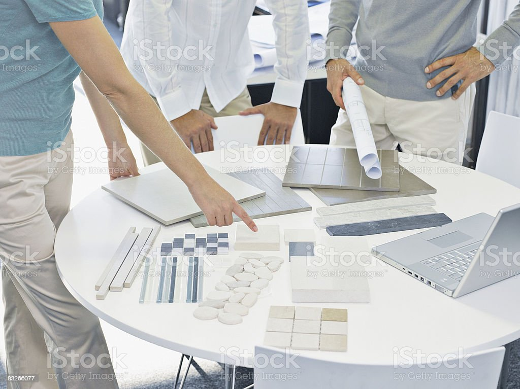 Interior designer talking with couple in showroom stock photo