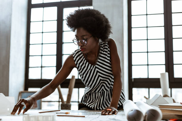 Interior designer wearing striped blouse working hard stock photo
