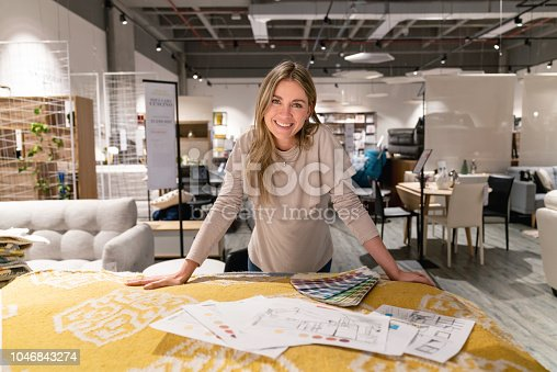 Portrait of a happy interior designer working on a home design at a furniture store and looking at the camera smiling. **DESIGN ON SKETCH WAS MADE FROM SCRATCH BY US**