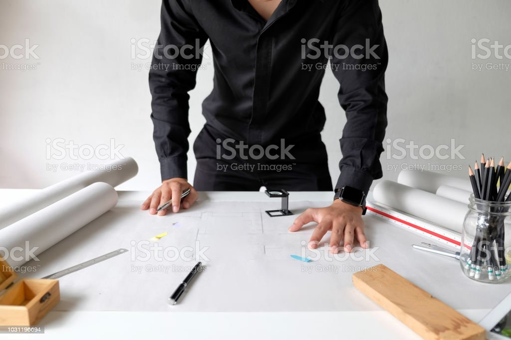 Interior Designer Working On The Blueprints At Creative