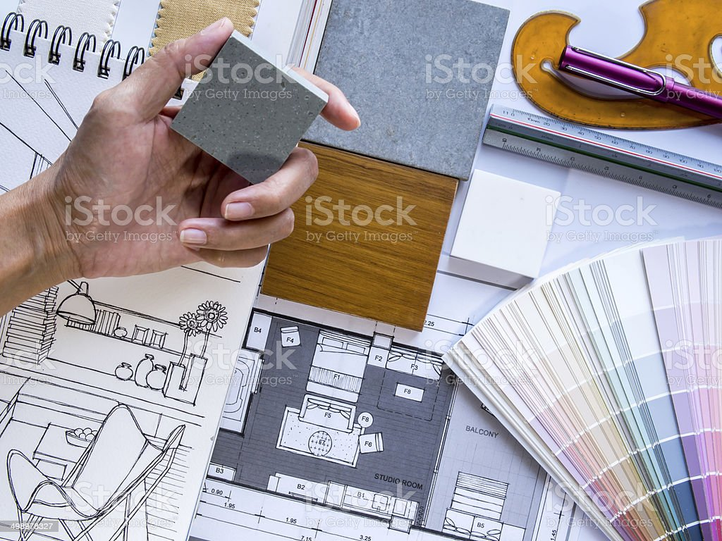 Interior designer's  hand working with illustration sketch and color samples stock photo