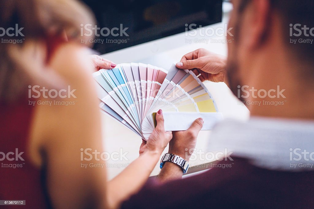 Interior designers pointing at color charts stock photo