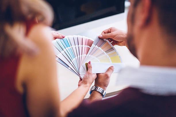 interior designers pointing at color charts - kleurenwaaier stockfoto's en -beelden