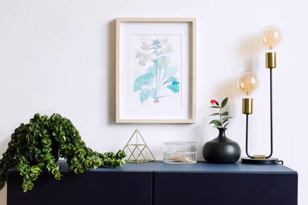 intérieur affiche floral mock up avec armature en bois vertical, lampe de table, accessoires, bougie, pyramide or et fleurs dans un vase noir sur le fond de mur blanc. concept avec étagère bleu marine. - camera sculpture photos et images de collection