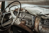 Interior with dashboard and instrumentation from an abandoned and very worn, beat up classic car from the fifties