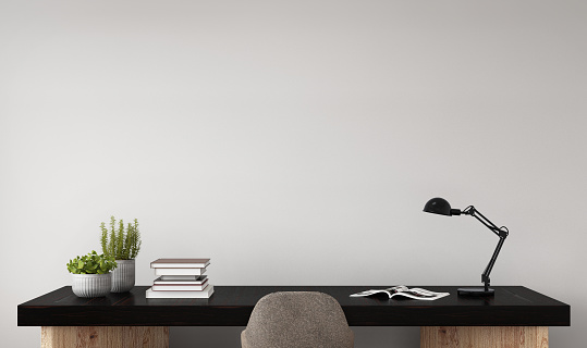 Office desk close up with chair. Empty gray wall template. Horizontal copy space interior setup. There is decoration, plant, table lamp, books, plants in a vase. Designer work background