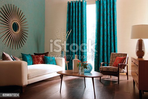Contemporary lounge / living room with sofa, curtains, table and vases