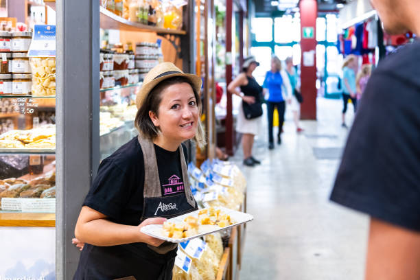 Interior indoor of Firenze Centrale Mercato central market with woman free samples Florence, Italy - August 30, 2018: Interior indoor of Firenze Centrale Mercato central market with people woman handing out serving free samples on tray mercato stock pictures, royalty-free photos & images