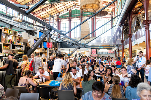 Interior, inside, indoor of Firenze Centrale Mercato, central market with crowd of people sitting on chairs by tables, eating food, drinks from cafes, restaurants