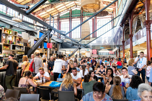 Interior, inside, indoor of Firenze Centrale Mercato, central market with crowd of people sitting on chairs by tables, eating food, drinks from cafes, restaurants Florence, Italy - August 30, 2018: Interior, inside, indoor of Firenze Centrale Mercato, central market with crowd of people sitting on chairs by tables, eating food, drinks from cafes, restaurants mercato stock pictures, royalty-free photos & images
