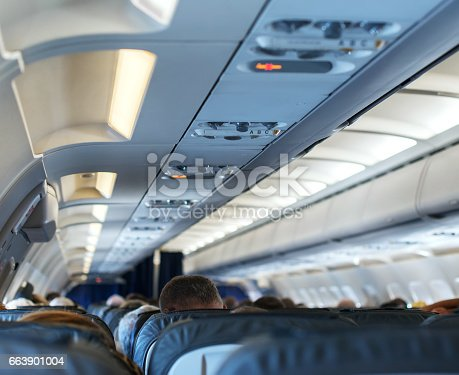 istock Interior inside of the plane with passengers. 663901004