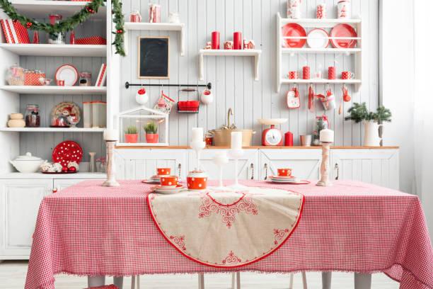 innen leicht graue küche und rote weihnachts-dekor. mittagessen zu hause auf das küchenkonzept vorbereiten. fokus auf tisch und wand - landküche stock-fotos und bilder
