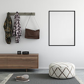 Interior of a home entrance with cushion seat, shelf with decoration and coat rack with clothes. carpet on the concrete floor. wall background with picture template for copy space. square composition.