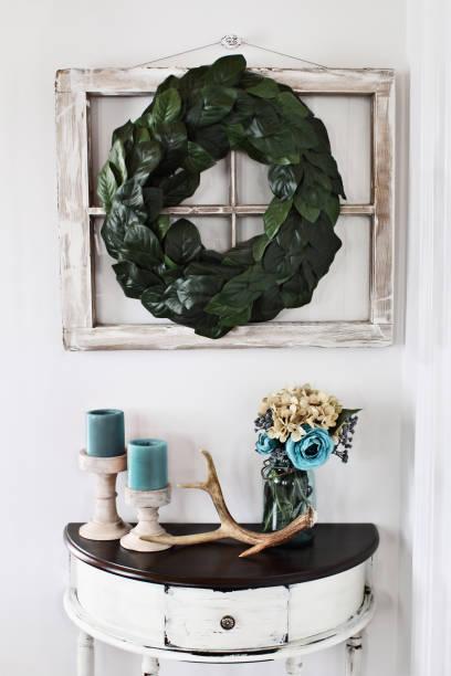 inneren magnolia blatt kranz über alte fenster mit tisch - rustikale einweckgläser stock-fotos und bilder