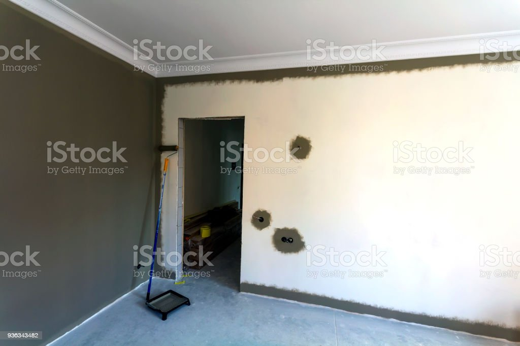 Interior of a apartement room during renovation work. Painting of the walls with dark paint. stock photo
