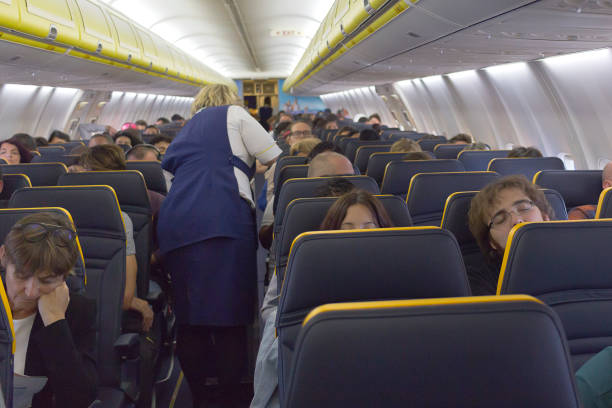 Interior of a Boeing Ryanair with passengers sit and stewardess in the aisle - Flight from Madrid to Milan - Defocused background stock photo